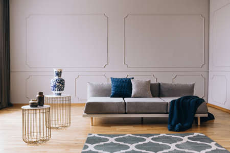 Blue blanket and pillows on grey comfortable sofa in designed living room interior with wooden floor and white wall
