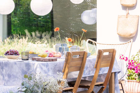 Wooden chairs at table with food on the terrace of house with flowers and lamps
