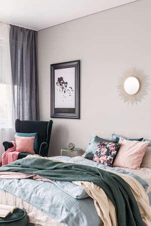 Forme de soleil comme un miroir et une carte dans un cadre noir sur un mur gris de l'intérieur de la chambre à la mode avec lit king size et literie confortable