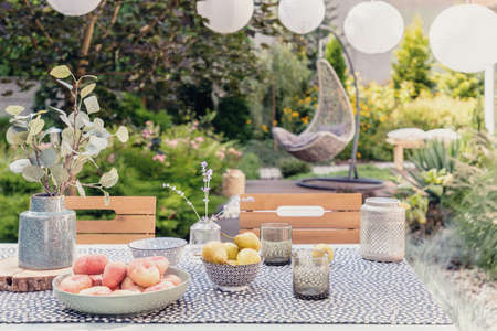 Plant and food on table in the garden with blurred hanging chair in the background Stock Photo