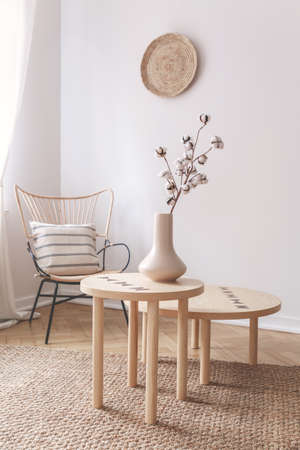 Cotton flower in beige vase on small wooden coffee table next to wicker chair with pillow