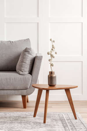 Cotton flower on stylish copper vase on small wooden coffee table next to grey settee Stock Photo