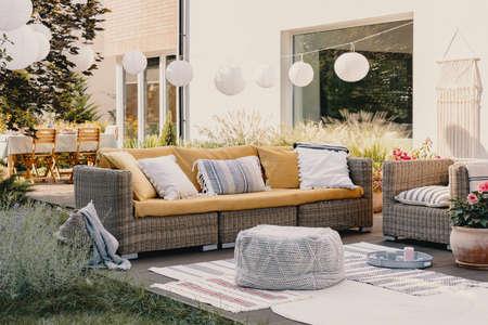 Poef naast rotan bank en fauteuil op houten terras met bloemen en lampen Stockfoto