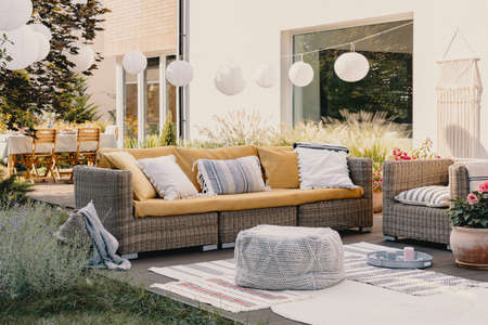 Pouf next to rattan couch and armchair on wooden terrace with flowers and lamps 스톡 콘텐츠 - 124959645