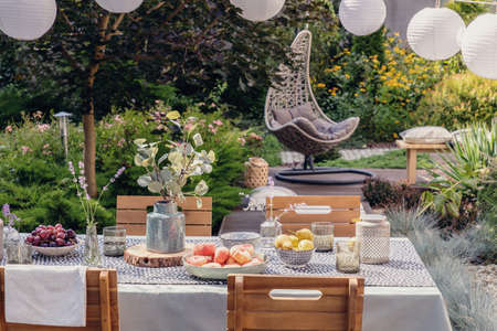 Table with flowers and food in the garden with hanging chair next to plants