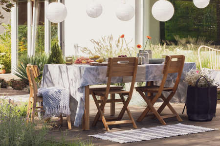 Rug next to wooden chairs at table with food on the terrace with lamps and flowers