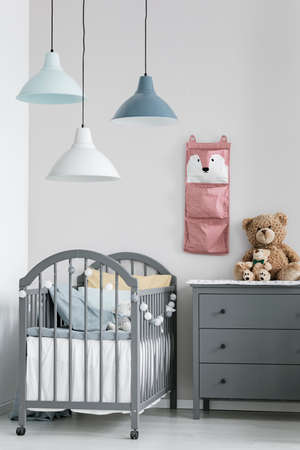Pink organizer on wall of trendy baby bedroom with two cribs and chest of drawers