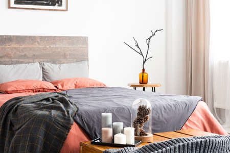 Candles and natural decorations standing next to wooden bed Stock Photo