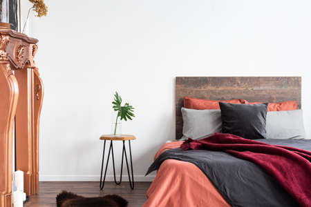 White interior with wooden bed, grey bedding, bedside table and coppery fireplace