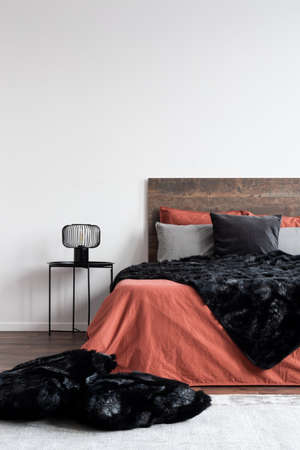 Black furry blankets and pillows on coral bedclothes in white bedroom