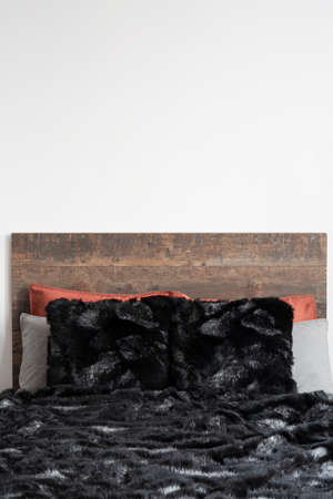 Close capture of black furry blanket on the wooden bed Stock Photo
