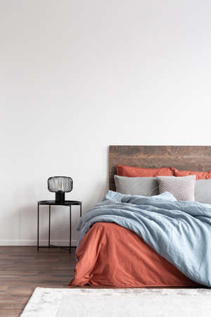 Minimal cozy interior with wooden bed with natural bedclothes on the empty white wall