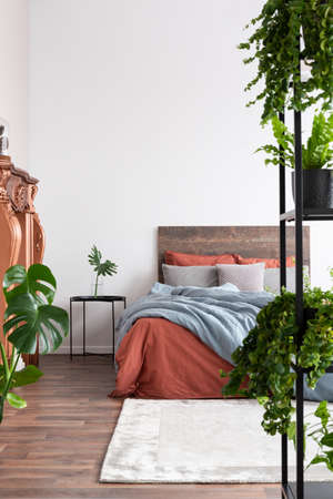 Eclectic bedroom with white walls, wooden bed, coral linen bedsheets and plants