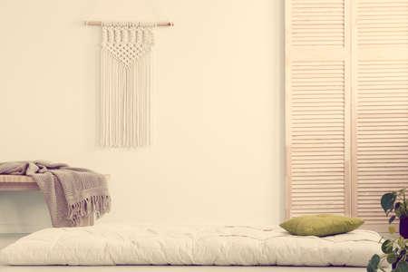 Handmade macrame on empty white wall of scandinavian bedroom interior Stock fotó