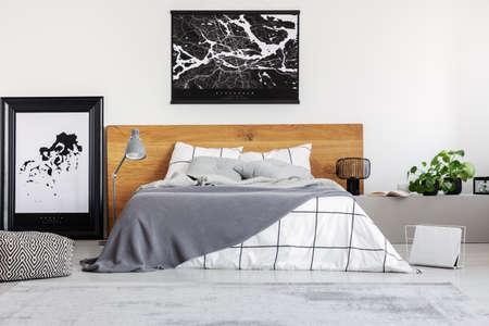 Schwarze Karte auf weißer Wand über dem Kopfteil aus Holz im einfachen Schlafzimmerinterieur