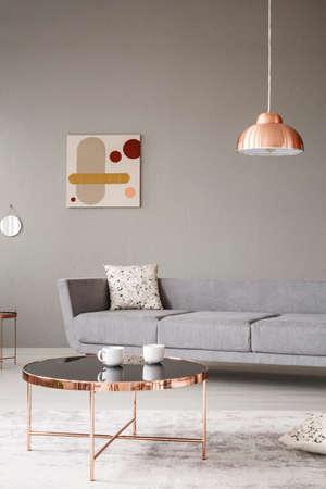 Luz colgante de cobre dorado sobre una alfombra gris del interior de una sala de estar minimalista con un gran sofá y una mesa brillante
