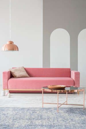 Geometric stencil shapes on a white wall of a fancy living room interior with a powder pink couch and shiny, golden decorations