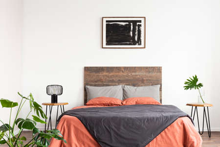 Bright natural interior with wooden bed and coral linen sheets Stock Photo