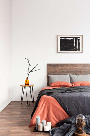 Comfy bed with grey and salmon bedding and pillows with bedside tables in white bedroom