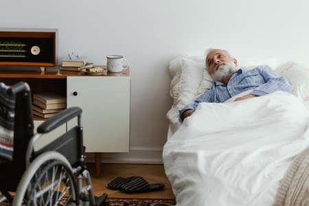 Sick elderly man wearing blue pajama lying in bed at nursing home Stock Photo