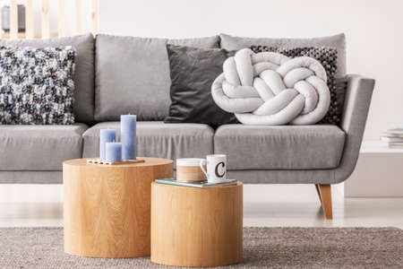 Two wooden coffee table with candles and mug in front of stylish Scandinavian couch with knot pillow Stock fotó