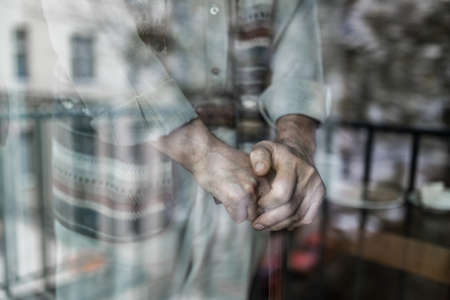 Through the glass shot of elderly man hands supported on wooden cane
