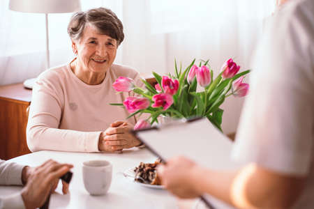 Smiling senior lady listening to her doctor in the nursing home