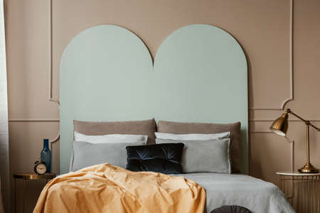 Pastel blue headboard of king size bed with cozy bedding and pillows Stock Photo