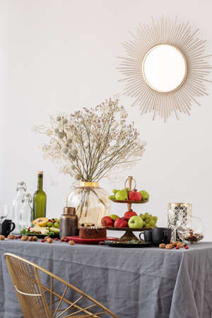 Common dining room table with food, fruits, cake and flowers in vase Reklamní fotografie