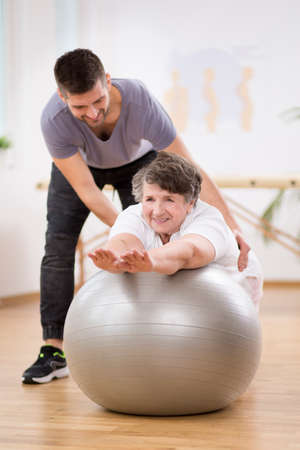 Smiling physiotherapy student helping senior woman lay on the exercising ball during rehabilitation Stock Photo