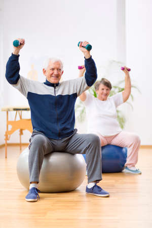 Two elderly patients exercising with weights in rehabilitation center