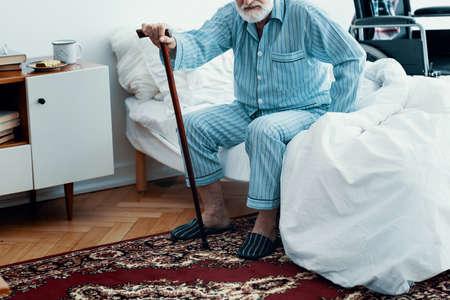 Alter kranker Mann mit grauem Bart und Haaren, der blaue Pyjamas trägt und zu Hause auf dem Bett sitzt