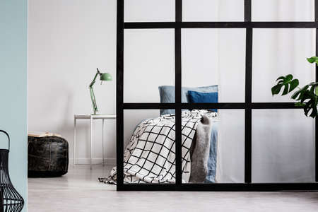Scandinavian bedroom interior with comfortable bed and mullions wall