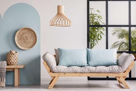 Wicker chandelier above wooden Scandinavian sofa with futon in bright living room interior 版權商用圖片
