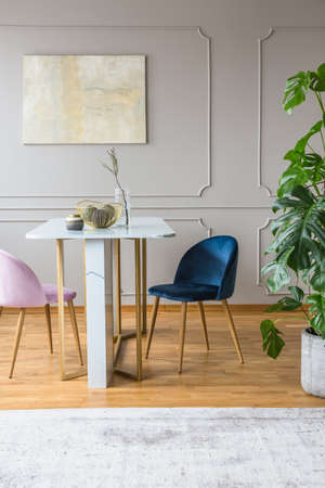 grey and gold table in dining room with pink and blue armchairs