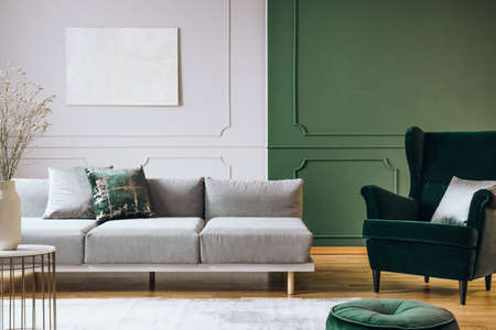Abstract oil painting on grey wall with moldings in contemporary living room interior with grey long couch
