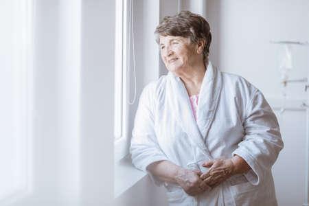 Senior grey lady wearing white bathrobe standing by the window at nursing home