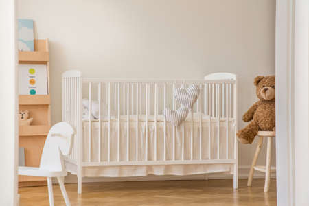 Teddy bear, rocking horse and white wooden crib with heart shaped pillows in scandinavian design interior, real photo with copy space