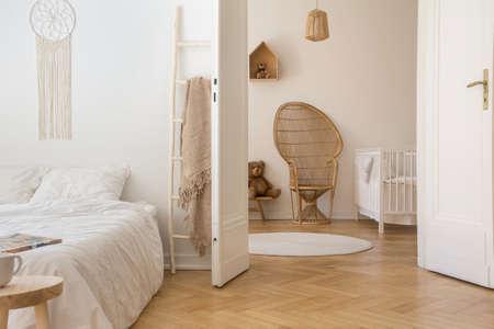 Scandinavische slaapkamer met wit beddengoed op het bed en deur open naar stijlvolle kinderkamer met witte houten wieg en rieten pauwstoel, echte foto