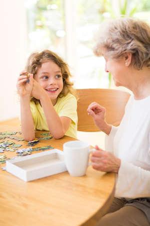 Junge und seine Großmutter bauen das Puzzle zusammen