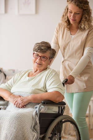 Positive senior patient on wheelchair with supportive nurse Stock Photo