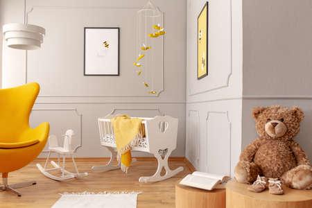 Krippe mit gelber Decke, Sessel, Teddybär in einem Kleinkinderzimmer. Echtes Foto Standard-Bild
