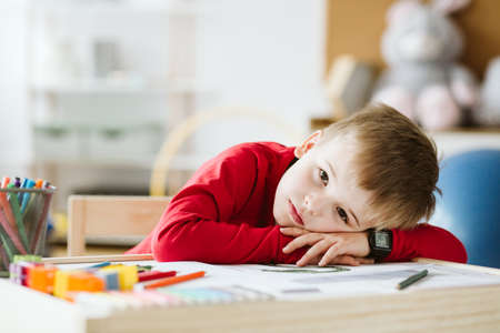 Sad little boy in red sweater feeling lonely and lying on a table Stockfoto