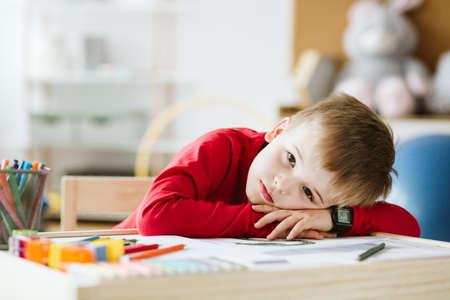 Trieste kleine jongen in rode trui die zich eenzaam voelt en op een tafel ligt