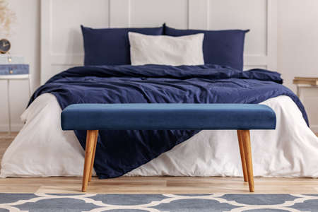 Navy blue velvet bench in the foot of king size bed in chic bedroom interior