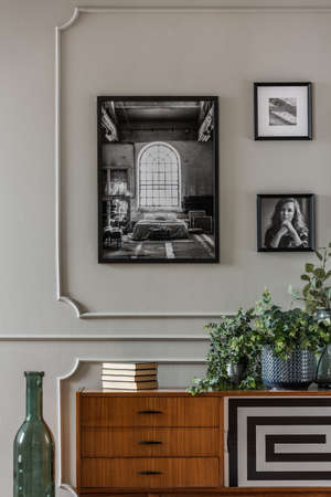 Close-up of a vintage, wooden sideboard with a geometric pattern standing against a gray wall with photos in living room interior. Real photo Stock Photo