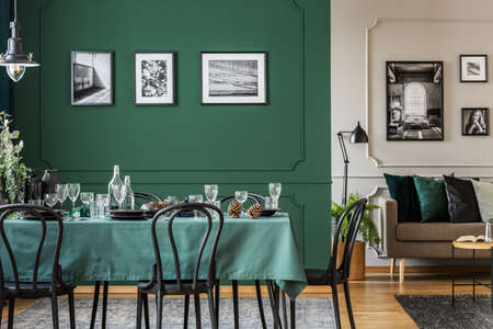 Modern, open space apartment interior with artistic, framed photos on green and white walls with molding. Real photo