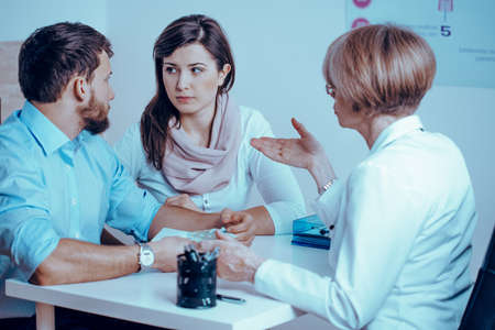 Worried couple consulting with female doctor on medical healthcare therapy 스톡 콘텐츠