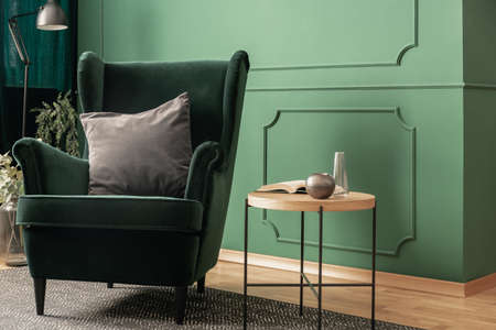 Close-up of a green velvet armchair with a gray cushion standing next to a wooden coffee table in a cozy living room interior with molding on the wall. Real photo