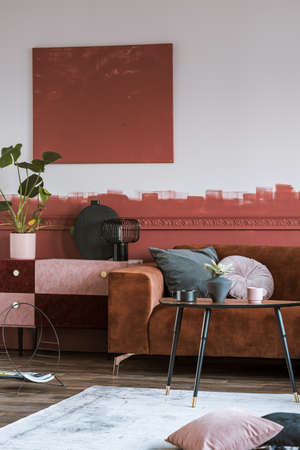 Suede burgundy and pastel pink commode with black vase with green leaf in classy living room interior